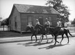 Three men riding horses