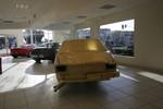 The Jewel / In God We Trust: junk car covered in gold leaf in luxury car dealer showroom