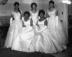 Five women wearing formal gowns