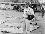 Fra flygtningelejr på en skoleplads i Cooch Behar, West Bengal, Nordindien. Arkitekt Niels Anton Dam ses her i flygtningelejren, midlertidigt opstillet af forhåndenværende materialer og presenninger. Skolens lokaler og redskabsrum er også fyldt med flygtninge. Skolen var lukket over 30 dage, da flygtningestrømmen kulminerede i maj-juni 1971, From the refugee camp at a school area of Cooch Behar, West Bengal, North India. The Architect