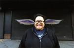 Celia Esguerra smiling and posing in front of a mural depicting angel wings