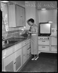 Jean Wilson cooks in kitchen, Los Angeles, 1930s