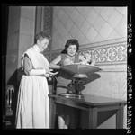 Helen Wolfe, Los Angeles Health Dept. director of nursing, in 1898 nurse's uniform helping weigh a baby using circa 1911 scale