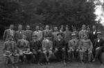 Fotografía de dos docenas de hombres al aire libre, la mayoría vistiendo trajes