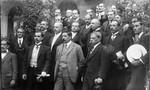 Varias filas de hombres en traje formal reunidos para una fotografía frente a un edificio