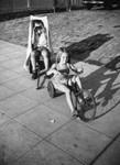 Two children playing on sidewalk