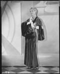 Peggy Hamilton modeling a black velvet dinner gown and metallic brocade jacket, 1930