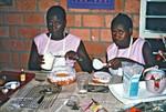Nordveststiftet, Tanzania, 1984. Et billede fra Gudrun Larsens hjem i Ntoma, hvor elever fra husholdningsskolen har lavet kager, som nu skal dekoreres. På Ntoma Husholdningsskole måtte man selv lave flormelis, da det ikke kunne købes i butikker, The North Western Diocese, Tanzania, 1984. A photo from Gudrun Larsen's home at Ntoma,. Student