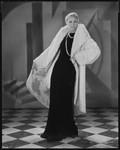 Peggy Hamilton modeling a white ermine coat over a black velvet evening gown, 1930