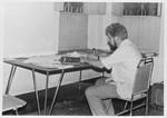 Saidpur, Bangladesh. Architect Niels Anton Dam was sent by Danida to Bangladesh, 1974-77, as he, Saidpur, Bangladesh. Arkitekt Niels Anton Dam var udsendt af Danida til Bangladesh, 1974-77, hvor han var leder af stort rehabiliterings-projekt for flygtninge. Her planlægger han arbejdet og studerer bengali. Skrivebordet er lavet i Saidpur af Rangpur Selvhjælps Service. (Foto november 1974)