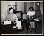 Two women sitting at typewriters