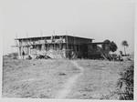 Formentlig Amnura, Øst Pakistan (fra 1971 Bangladesh), december 1966. Den nye bolig til sygeplejersker m.v. Huset forventes færdig omkring februar, 1967. Bygningshåndværkere har travlt med at pudse vægge og støbe det sidste af taget. Derefter skal der lægges knuste teglsten, blandet med lim, på taget - for at forhindre, at solen varmer for meget igennem, og for at gøre taget skråt, så regnvandet kan løbe af. (Huset kommer, sammen med medicinudsalg/apotek etc. til at koste omkring 60.000-70.000 Rps), Probably Amnura, East Pakistan (from 1971 Bangladesh), December 1966. The new Nursing station/a
